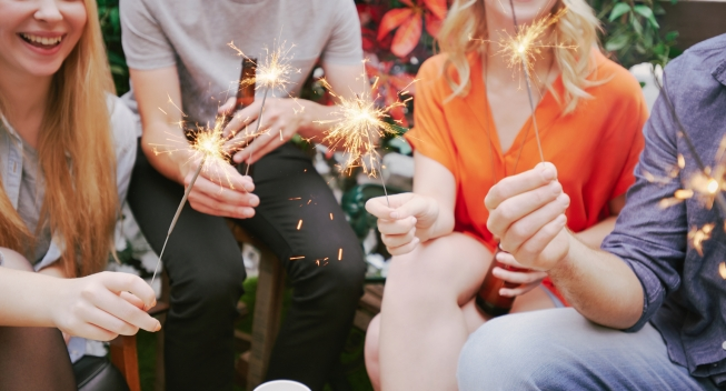 Friends having fun with sparkler at a party