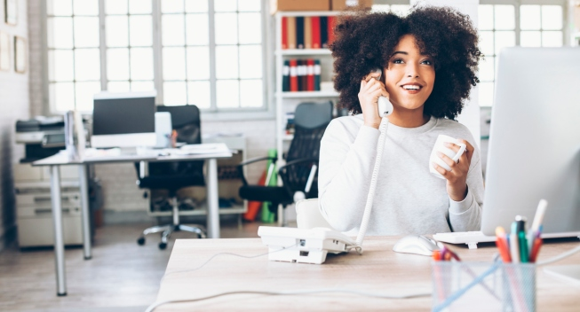 Smiling young businesswoman talking on the phone at workplace