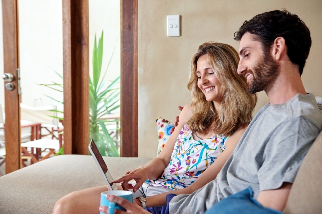 Smiling couple with tablet computer on sofa couch at home