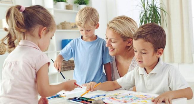 Children painting with teacher in preschool, Selective focus