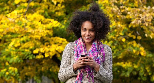 Portrait of a smiling young woman holding mobile phone outdoors
