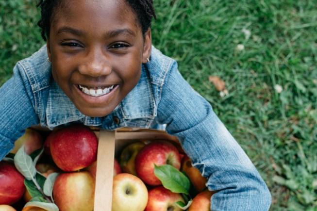 Smiling black girl with apple basket