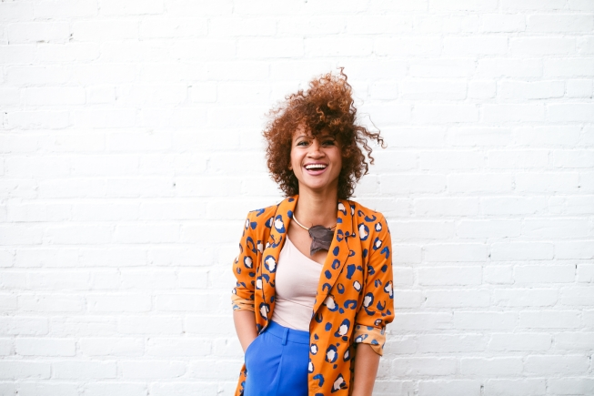 A young, beautiful woman with curly hair laughing against a white brick wall