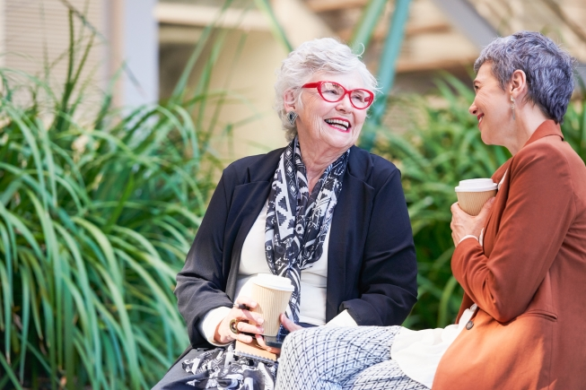 Two old ladies having coffee and fun on a day out