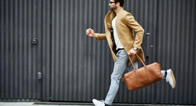 Businessman with bag running on sidewalk in city