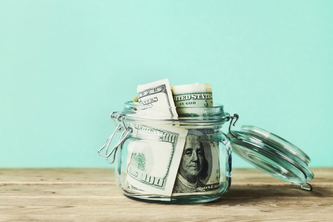 Dollar bills in glass jar on wooden table. Saving money concept.