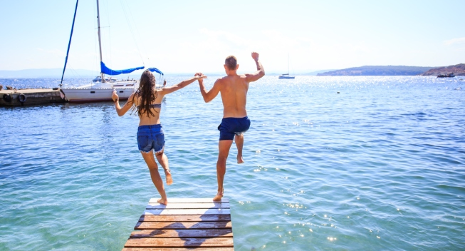Rear view of couple holding hands and jumping into water from a pier.