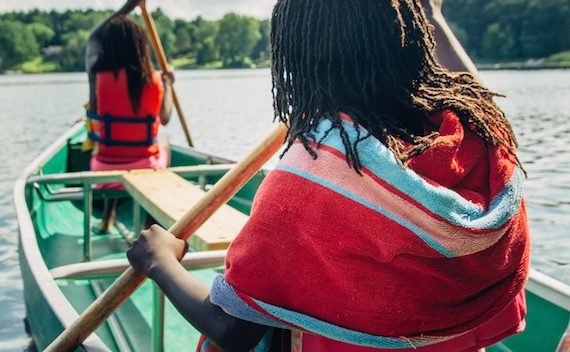 Two black girls paddling in a canoe