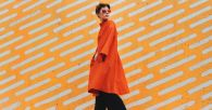 Urban Stylish Short Hair Female Model In Red/orange Coat In Front Of Orange Background.