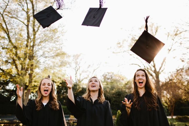 This is an image of female graduates throwing their caps into the air