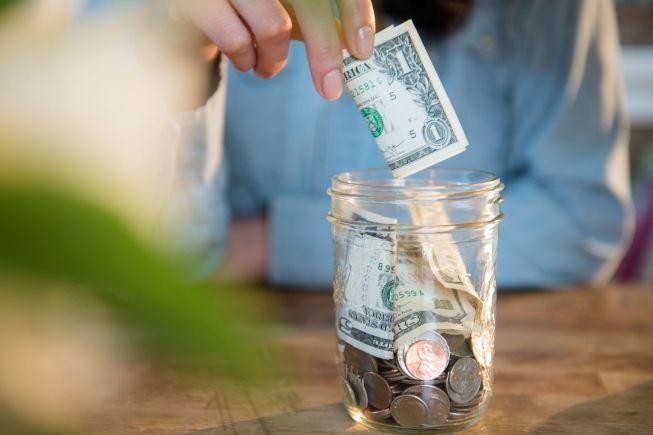 Woman putting money into savings jar