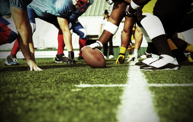 The blue, red, and white football team line up at the line of scrimmage against the black and yellow team.  The play is about to begin as the center has hand on the football and is ready to snap to the quarterback.  Photo perspective is low and between the two teams.