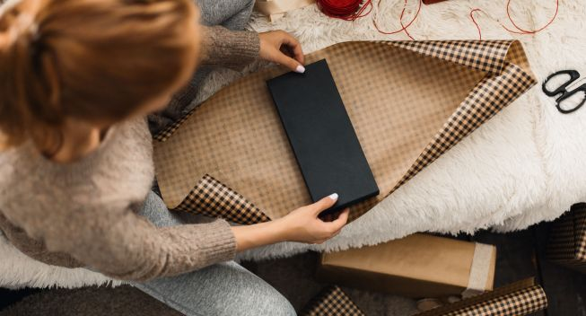 Young redhead woman wrapping Christmas Gifts at home