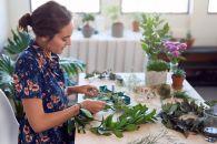 Young beautiful woman creating making christmas decorations, crafting xmas wreaths