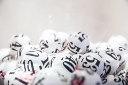 Many white lottery balls with black numbers on them are close together. Close up shot is taken against a white background. Taken by Canon 5D Mark lv.