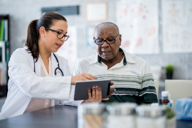 A senior man of African descent is indoors in a hospital room. He is watching his female doctor using a tablet computer. She is explaining a medication schedule to him.