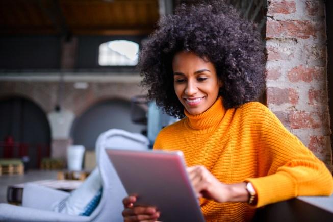 Smiling African American woman using digital tablet.