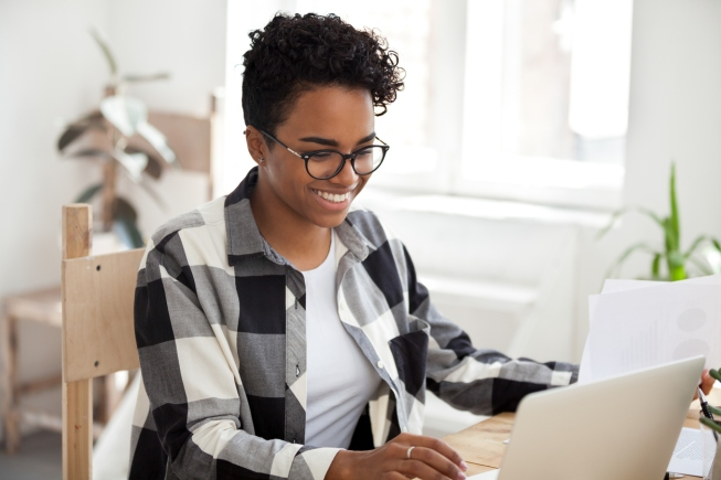 Smiling black woman sit at desk working at laptop review paperwork documents, happy African American female using computer managing financial papers, girl in glasses studying or chatting on pc