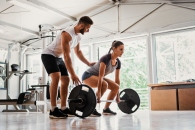 Young woman with instructor preparing for deadlift
