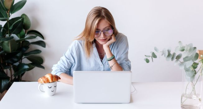 Closeup side portrait of young blonde beautiful woman working, browsing internet, chatting, texting and listening music with laptop at home having coffee and croissant, looking happy and relaxed.