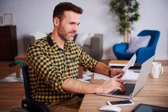 Side view of disabled businessman using laptop in home office