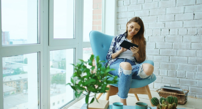 Attractive girl using digital tablet sitting in chair at balcony in loft modern apartments