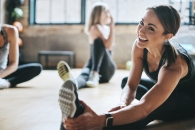 Shot of mature women stretching with a young female instructor during a training class at the gym
