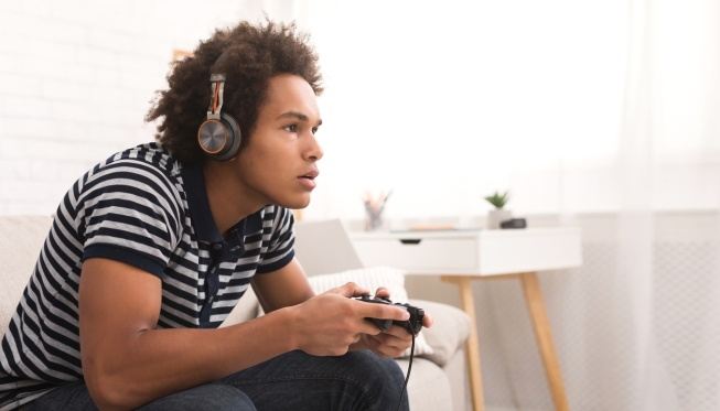Concentrated teenager playing video games with joystick at home, copy space