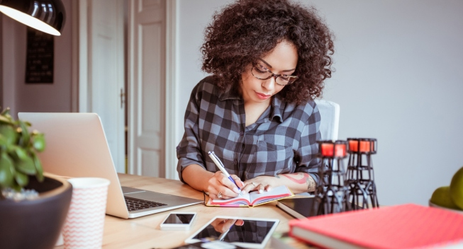 Shot of afro american woman in a home office taking notes in diary. Businesswoman sitting at table and working from home office.