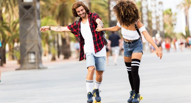 Shot of beautiful young couple skating with rollerblades in the street.Full length of happy urban couple in knee socks entertaining together on rollerblades in summer.