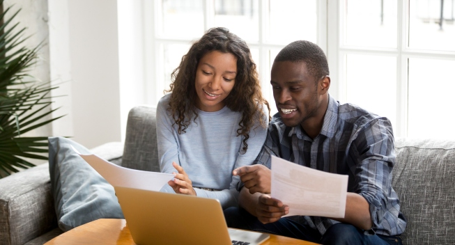 African black positive married couple sitting on sofa at home read documents paper checking bills, bank account balance feeling satisfied and happy. Refund income last loan payment good news concept