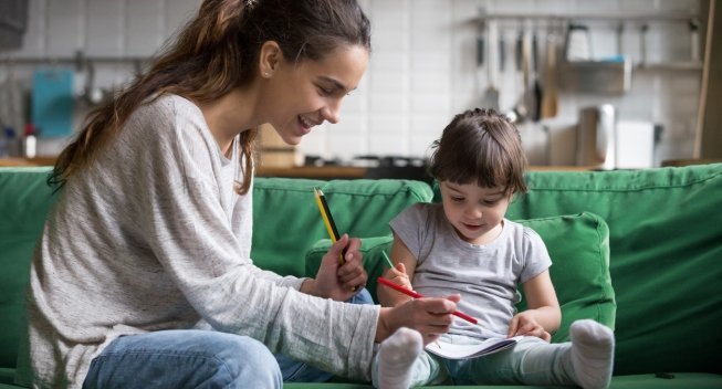 Smiling nanny and preschool kid girl drawing with colored pencils sitting on sofa together